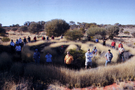 25 people stand in a growth ring of a spinifex clump in the Great Victoria Desert