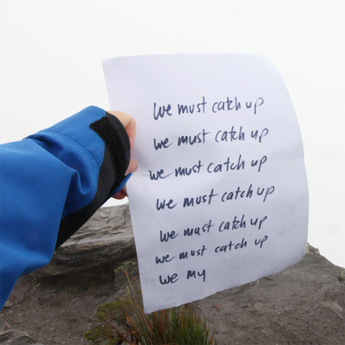 a hand holds a piece of paper at the top of a mountain