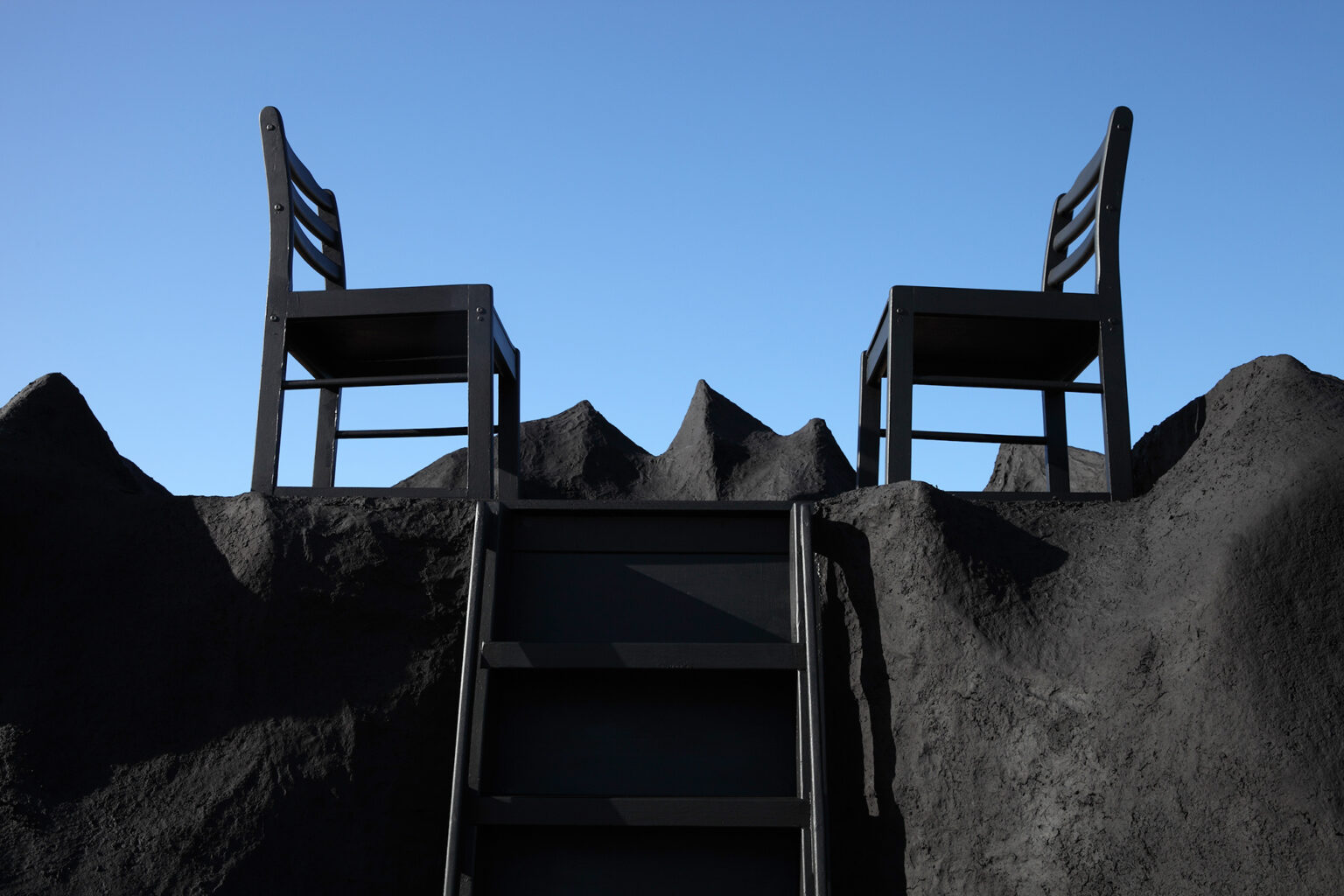 two chairs on the top of a mountaqin